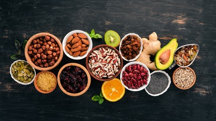 Various superfoods. Dried fruits, nuts, beans, fruits and vegetables. On a black wooden background. Top view. Free copy space.