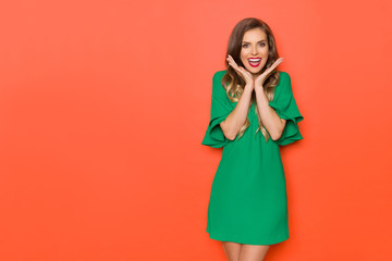 Happy Young Woman In Green Mini Dress Is Holding Head In Hands And Shouting