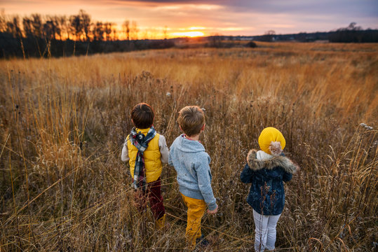 Three children standing in a field at sunset, United States