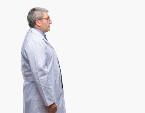 Handsome senior doctor, scientist professional man wearing white coat over isolated background looking to side, relax profile pose with natural face with confident smile.