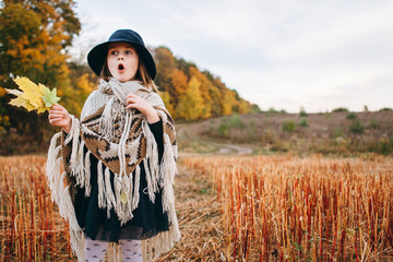 Little girl in poncho and hat traveler in the field with orange and red grass.