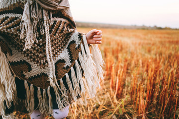 Atmospheric autumn background. Poncho on a girl in a field with several leaves. Girl in autumn mood