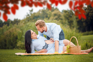 young couple having a picnic in a city park, a woman is expecting a baby.