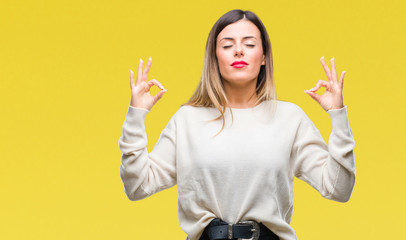 Young beautiful woman casual white sweater over isolated background relax and smiling with eyes closed doing meditation gesture with fingers. Yoga concept. Wall mural