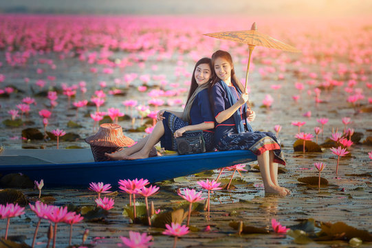 Two women sitting on a boat in a lotus flower lake, Thailand
