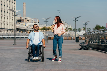 handsome boyfriend in wheelchair and girlfriend with disposable coffee cup having walk on street