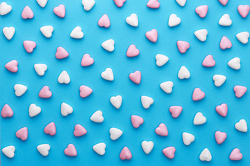 Heart shaped candies pattern on a blue background. Top view
