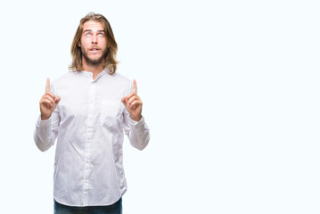 Young handsome man with long hair over isolated background amazed and surprised looking up and pointing with fingers and raised arms.
