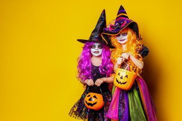 Two Beautiful girls in a witch costumes and hats on a yellow background scaring and making faces. Portrait of little girls in carnival costumes of sorceress, background on halloween.