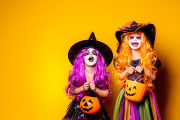 Two Beautiful girls in a witch costumes and hats on a yellow background scaring and making faces. Portrait of little girls in carnival costumes of sorceress, background on halloween. Fototapete