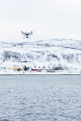 Norway. Small drone in flight over Norwegian fjord.