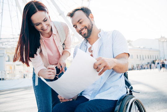 smiling handsome boyfriend in wheelchair and girlfriend looking at map on street