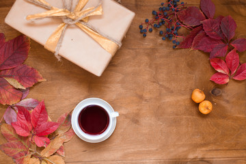 Autumn leaves a cup of tea and coffee gift on wooden background