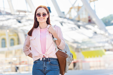 portrait of happy attractive woman in pink sunglasses and clothes looking at camera on street