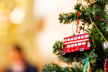 Fir tree decorated with toy double decker bus and light bulbs for Christmas and New Year celebration.