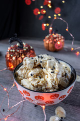Halloween ice cream in pumpkin bowl with background decorations and lights
