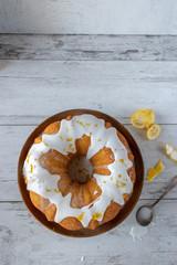 lemon bundt cake with white glaze on cake stand flat lay