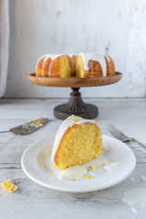 lemon bundt cake with white glaze on cake stand with cake slice
