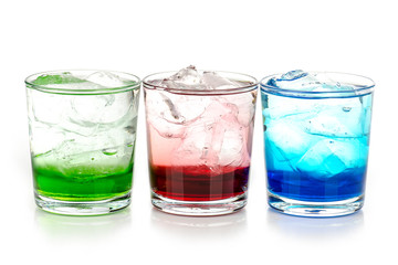 green, blue and red drink with ice cubes on white background
