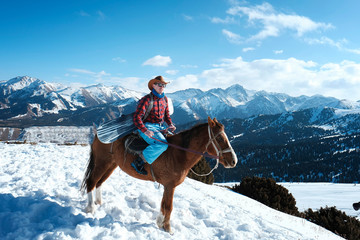 A man is a cowboy on a horse. Winter. the mountains.