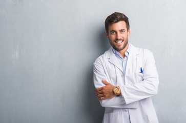 Handsome young professional man over grey grunge wall wearing white coat happy face smiling with crossed arms looking at the camera. Positive person.