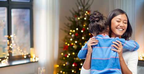 family, holidays and happiness concept - happy mother hugging her daughter over christmas thee lights background