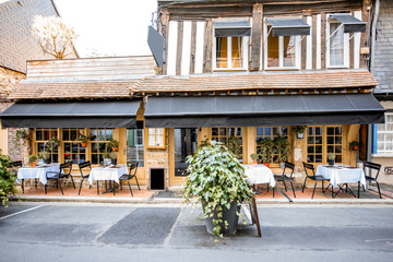 Old building facade with beautiful restaurant in Honfleur, famuos french town in Normandy