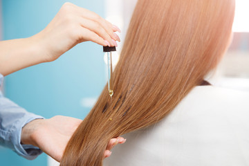 Master hairdresser applies oil to hair care for and restore growth of cuticles woman.