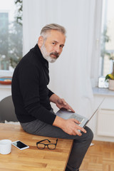 Pensive businessman perched on his desk