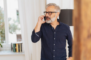 Senior man talking on a mobile phone indoors