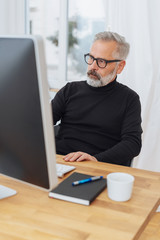 Businessman staring intently at a desktop monitor