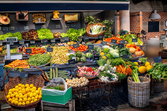 Variety of beautifully organized fruits and vegetables on the counter of the market place