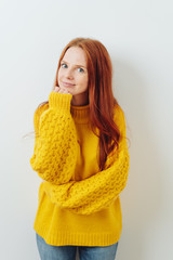 Pensive young redhead woman in a yellow sweater