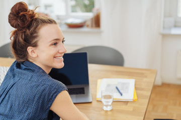 Happy young businesswoman sitting in an office