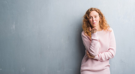 Young redhead woman over grey grunge wall wearing pink sweater looking at the camera blowing a kiss with hand on air being lovely and sexy. Love expression.
