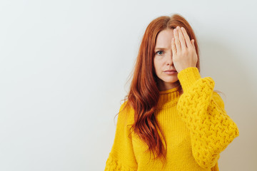 Young redhead woman covering one eye