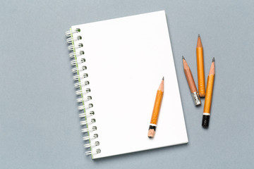 Pencils and notepad paper sheets on gray desk table