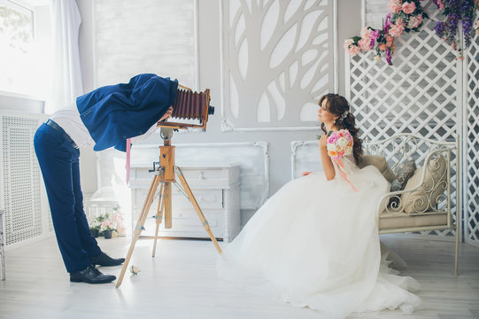 The groom photographs the bride on a vintage camera
