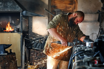 Brutal worker cuts a detail with an angle grinder in a forge workshop