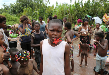 Congolese migrants expelled from Angola who crossed the border wash their clothes in a river near Kamako, Kasai province