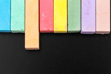 Set of colored chalks over a black background