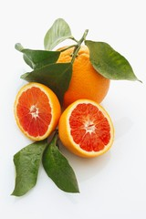 Blood oranges, whole and halved, with leaves