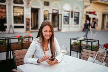 Beautiful young brunette using phone while sitting in outdoors restaurant.