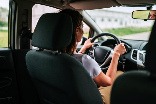 Lifestyle shot of young cheerful woman driving car, rear view.