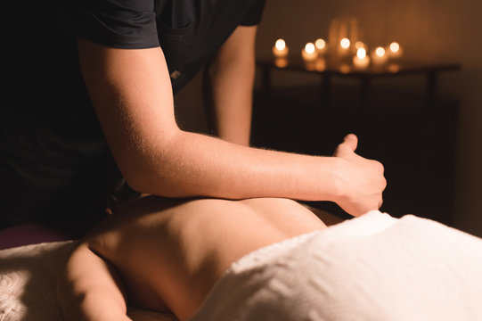 Close-up Spa massage low angle. male massage therapist doing a back and shoulder massage to a young girl with her elbows in a dark office amid burning candles