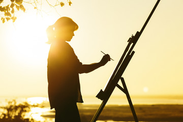 silhouette of a woman painting a picture with paints on canvas on an easel, girl with paint brush and palette engaged in art on the nature in a field at sunset