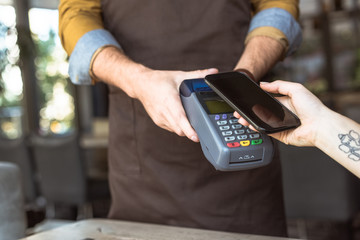 cropped shot of waiter holding payment terminal while customer doing contactless purchase with smartphone in cafe