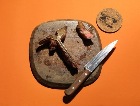The leftovers of a T-bone steak on a wooden board