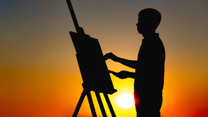 silhouette of a man painting a picture with paints on canvas on an easel on nature, boy with paint brush and palette engaged in art at sunset