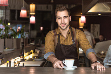 attractive young barista with cup of delicious coffee looking at camera